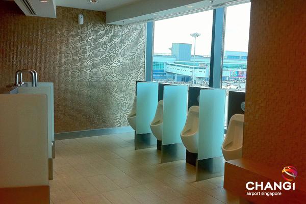 Banheiro masculino com vista para o pátio dos aviões