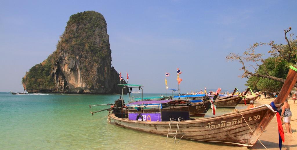 Praia de Railay Beach com água verde azulada com os típicos barcos tailandezes e uma pedra pontuda ao fundo