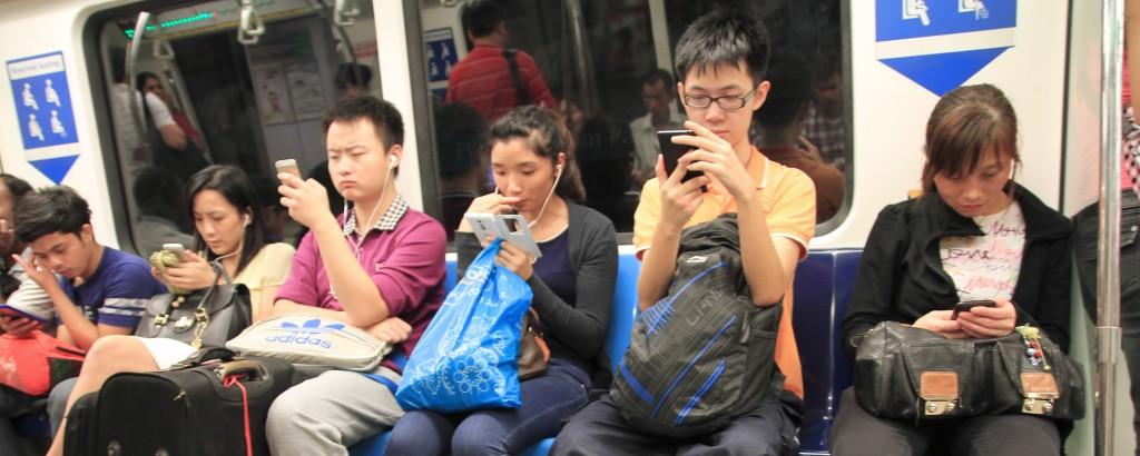 Passageiros de um metro olhando para seus celulares