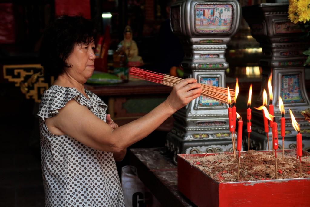 Mulher acendendo velas em um templo taoista