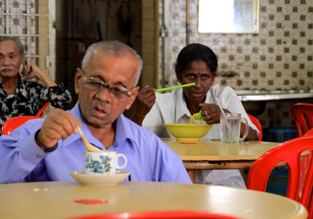 # pessoas de etinias diferentes comem juntas em um restaurante em Kuala Lumpur