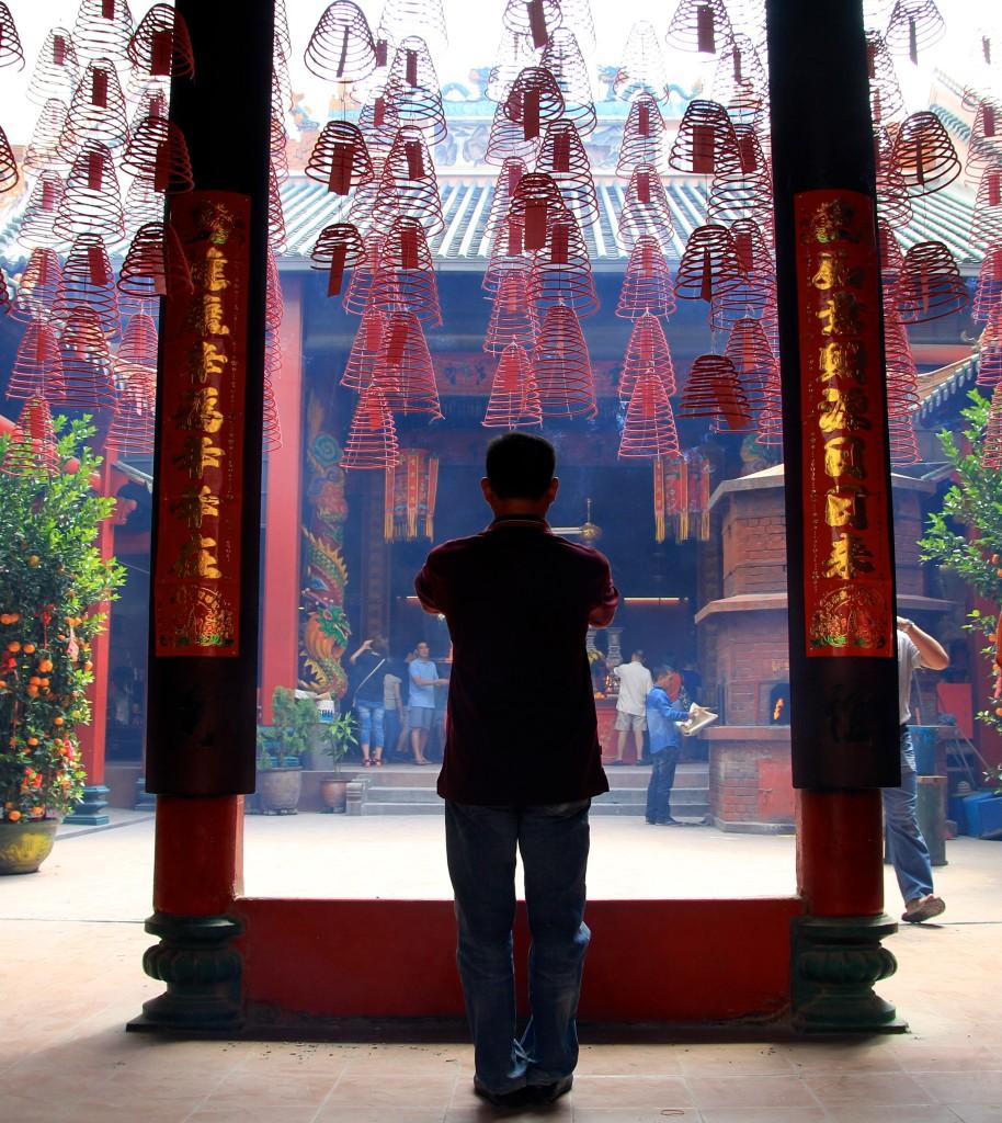 Homem reza em frente a um templo taoista em Kuala Lumpur