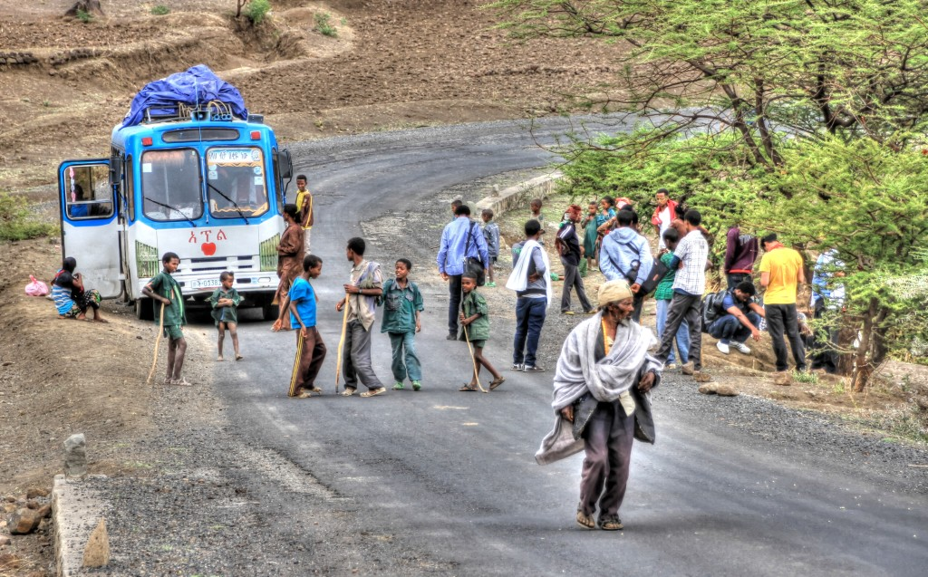 ônibus encostado na estrada na Etiópia com o pneu furado
