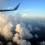 Da janela de um avião, a vista para as nuvens e o mar ao entardecer